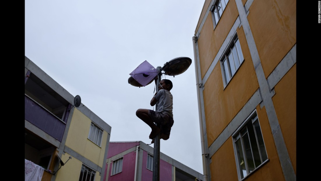 "A child tries to retrieve his kite snagged on a lamppost in the Rocinha favela. ""Kites are playful; they are meant to soar in the air,"" Bastianelli said. ""This one was tangled, much like the favela's residents continue to be in Rio's ongoing 'war on drugs' between the police and the gangs."""