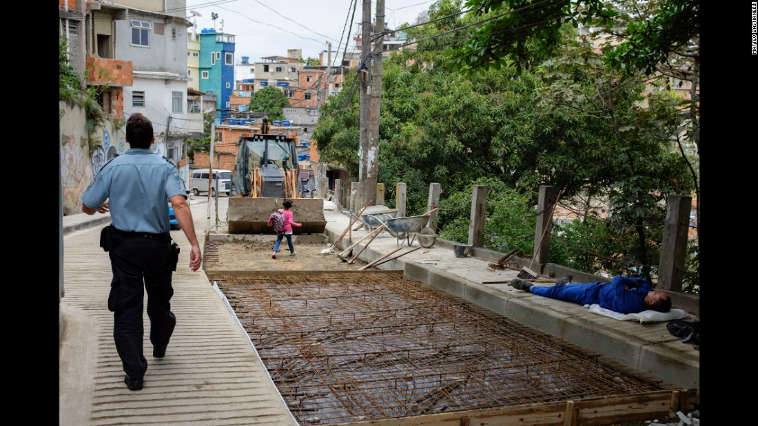 A police officer walks through Cantagalo while a little girl heads past a construction site on her way home from school.