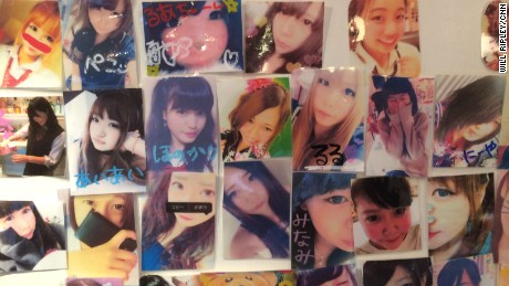 A wall showing photos of young women in a Japanese schoolgirl cafe.