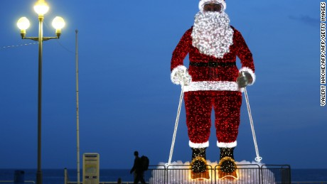 "TOPSHOT - A giant illuminated Santa Claus model is displayed along the ""Promenade des Anglais"" in the French Riviera city of Nice, southeastern France, on December 12, 2015.  / AFP / VALERY HACHE        (Photo credit should read VALERY HACHE/AFP/Getty Images)"