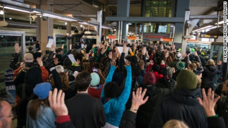 "MINNEAPOLIS, MN -  DECEMBER 23:  Black Lives Matter protestors hold their hands in the air and chant, ""Hands up, don't shoot,"" at the Minneapolis-St. Paul International airport Lightrail stop on December 23, 2015 in Minneapolis, Minnesota. Black Lives Matter Minneapolis staged a brief protest at the Mall of America in Bloomington, MN before moving their protest to the airport. (Photo by Stephen Maturen/Getty Images)"