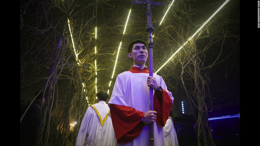 A cross-bearer attends a Christmas Eve Mass at a Catholic church in Beijing on Thursday.