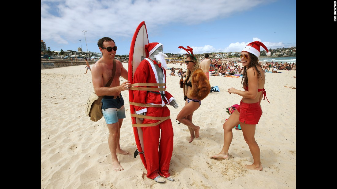 A mannequin in a Santa costume is strapped to a surfboard for easy transport along Bondi Beach as Tom Ray, left, of Britain, Ashley Pronyk of Canada, center, and Helen Maine of Britain celebrate Christmas in Sydney, Australia.