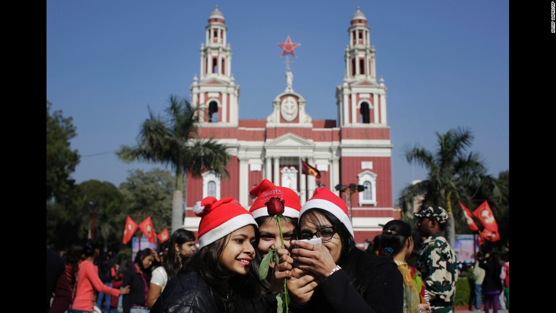 Girls look at photos after taking selfies in front of the Sacred Heart Cathedral in New Delhi on December 25.