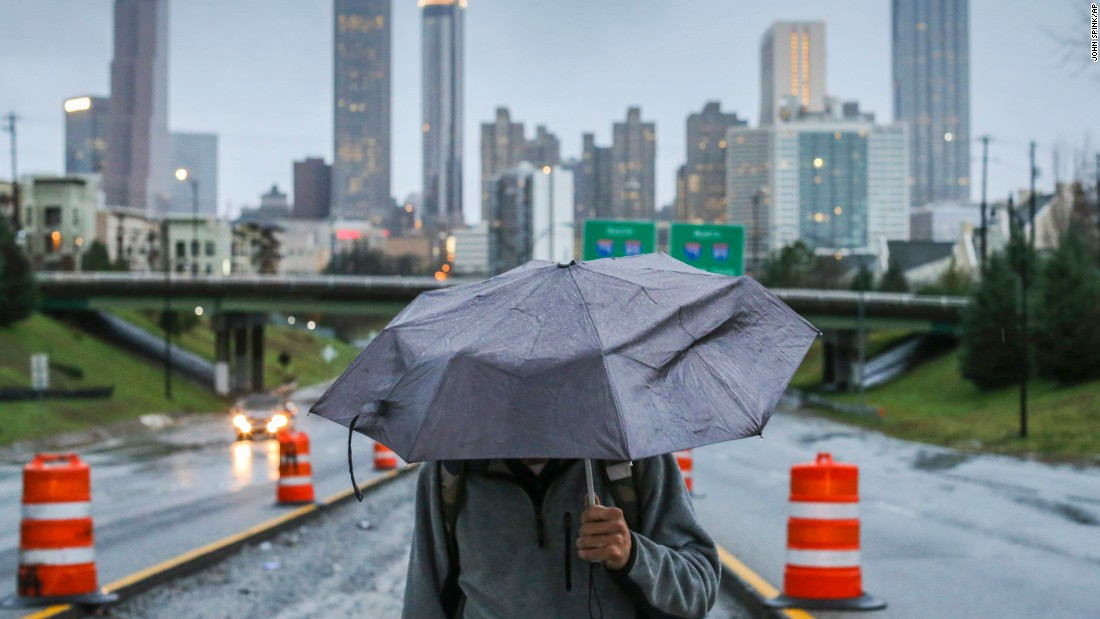 A man walks near downtown Atlanta in the rain on Thursday, December 24. Georgia Gov. Nathan Deal declared a state of emergency in three north Georgia counties amid the strong storms.