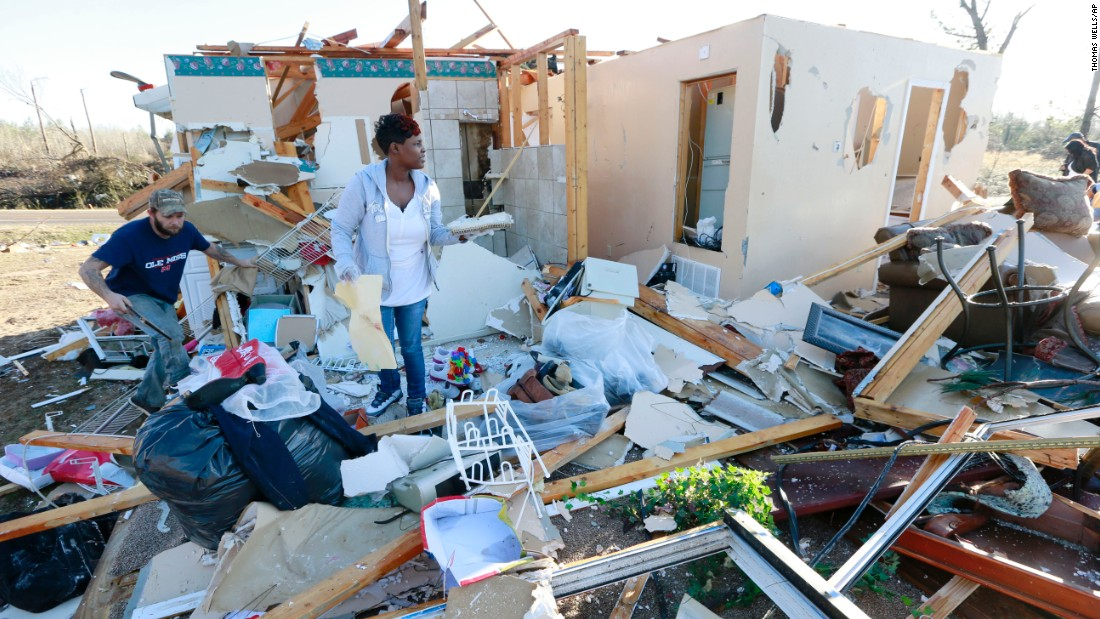 Trista Boga, center, helps salvage what she can from a friend's home along Highway 178 in Holly Springs, Mississippi, on Thursday. At least 14 people were killed in Mississippi, Tennessee and Arkansas as spring-like storms mixed with unseasonably warm weather and spawned rare Christmastime tornadoes in the South.