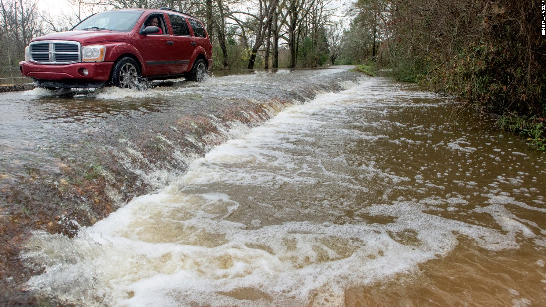 A vehicle drives along a flooded section of Hayneville Road in west Montgomery, Alabama, on Christmas morning.