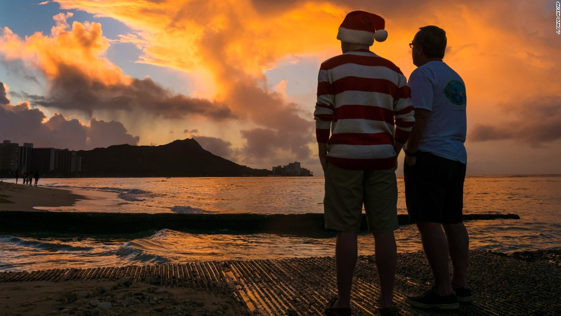 Tourists watch the Christmas Day sunrise behind Diamond Head from Waikiki Beach in Honolulu.
