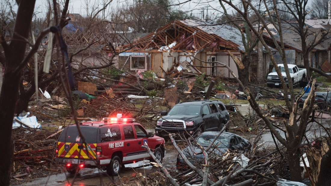 An emergency vehicle drives through a neighborhood in Rowlett, Texas, on Sunday, December 27. Crews were scouring debris for victims and assessing damage.