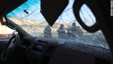 Afghan security personnel are seen through the shattered windshield of a damaged car after a suicide car bomb attack near the Kabul airport in Kabul, Afghanistan, Monday, Dec. 28, 2015. Taliban spokesman Zabihullah Mujahid claimed responsibility for the attack, and said the target of the suicide bomber was a convoy of foreign forces. (AP Photo/Rahmat Gul)