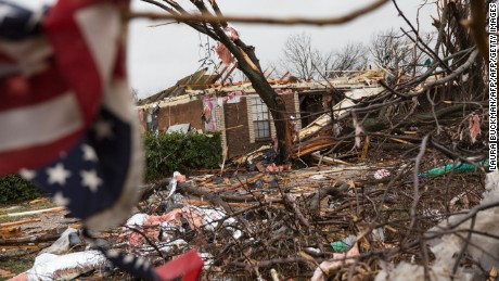 An American flag placed by first responders is seen December 27, 2015 in the aftermath of a tornado in Rowlett, Texas.  At least 11 people lost their lives as tornadoes tore through Texas, authorities said, as they searched home to home for possible more victims of the freak storms lashing the southern United States. The rare December twisters that flattened houses and caused chaos on highways raised the death toll from days of deadly weather across the South to at least 28. AFP PHOTO/LAURA BUCKMAN / AFP / LAURA BUCKMAN        (Photo credit should read LAURA BUCKMAN/AFP/Getty Images)