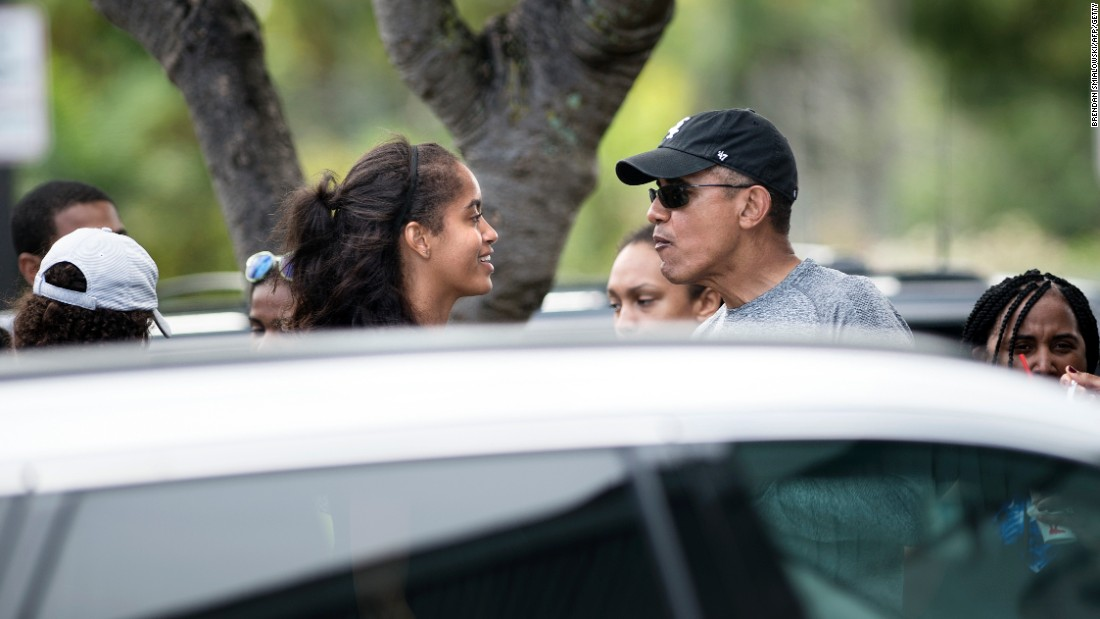 Obama talks with his daughter Malia while stopping for shave ice at Island Snow.