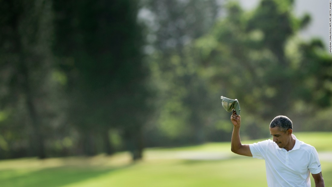 Obama tips his hat after finishing the 18th hole at the Mid Pacific Country Club golf course.