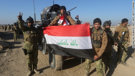Members of Iraq's elite counter-terrorism service pose with their national flag on December 29, 2015 in the city of Ramadi after Iraqi forces recaptured it from ISIS fighters.