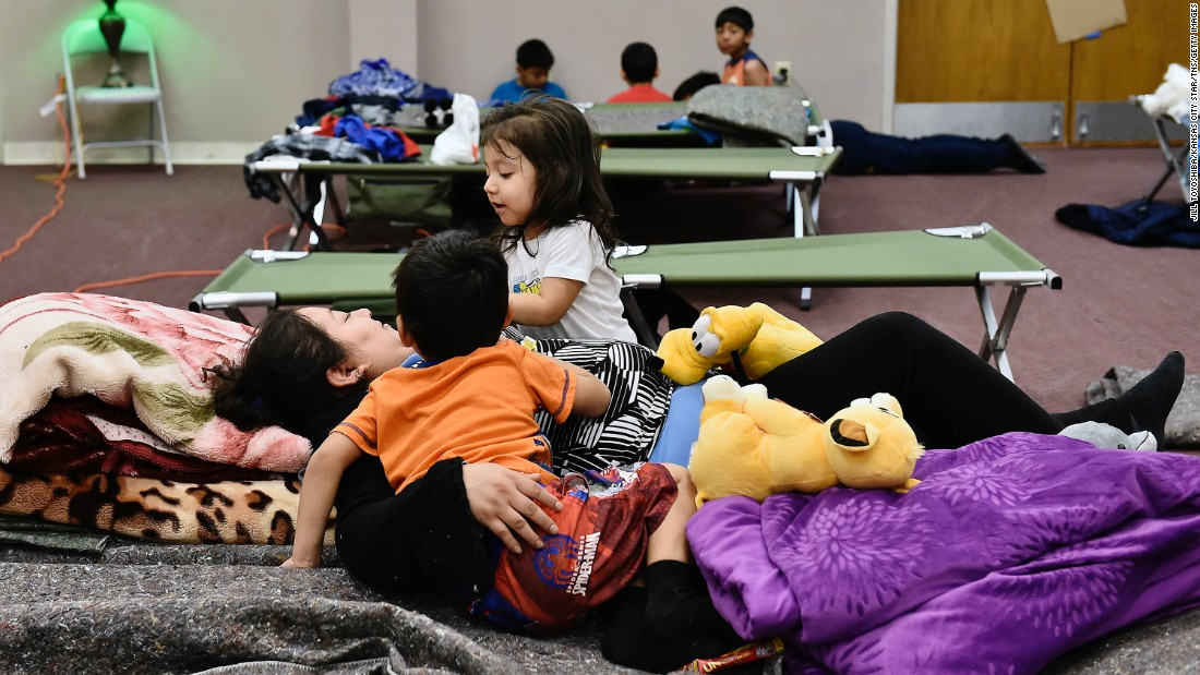 A family displaced by flooding passes time on December 29 at Fairview Christian Church in Carthage, Missouri, where the Red Cross set up a shelter.