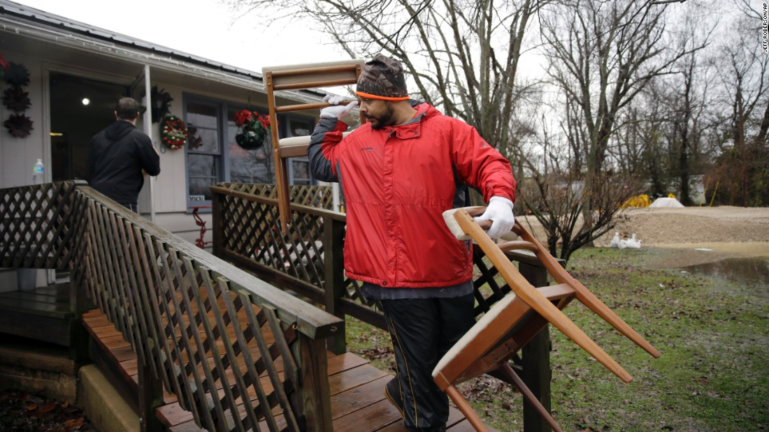 Men help move furniture out of a gift shop as a precaution on December 28 in Kimmswick.
