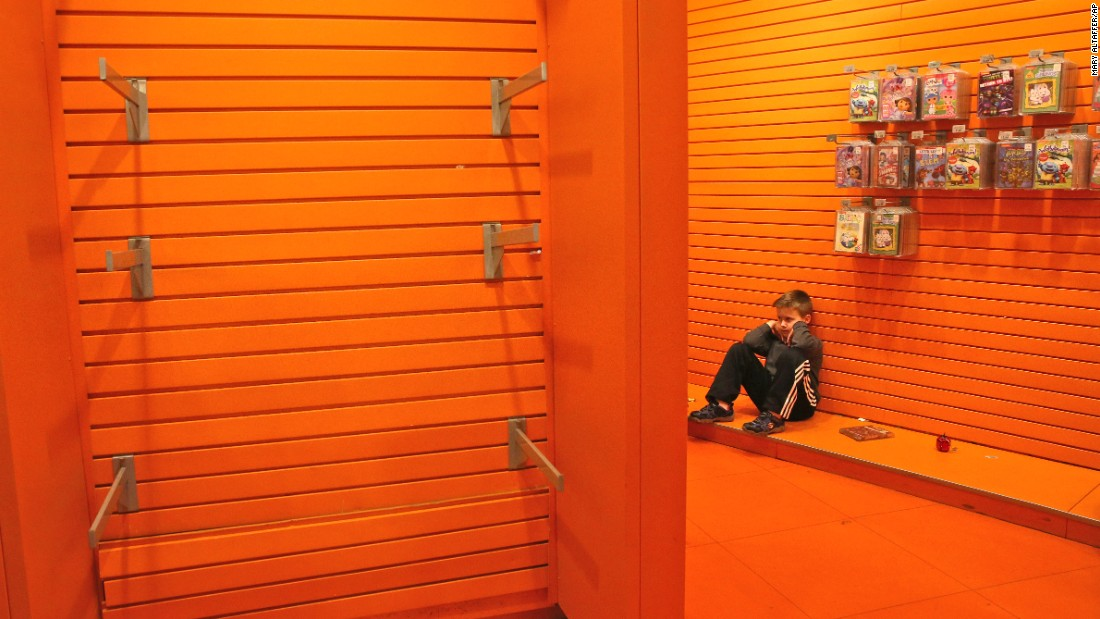 "A child sits next to empty toy displays at the Toys R Us store in New York's Times Square on Wednesday, December 30. It was <a href=""http://money.cnn.com/2015/12/30/news/companies/toys-r-us-times-square/"" target=""_blank"">the last day of business</a> for the flagship store, which was closing up shop after 14 years."