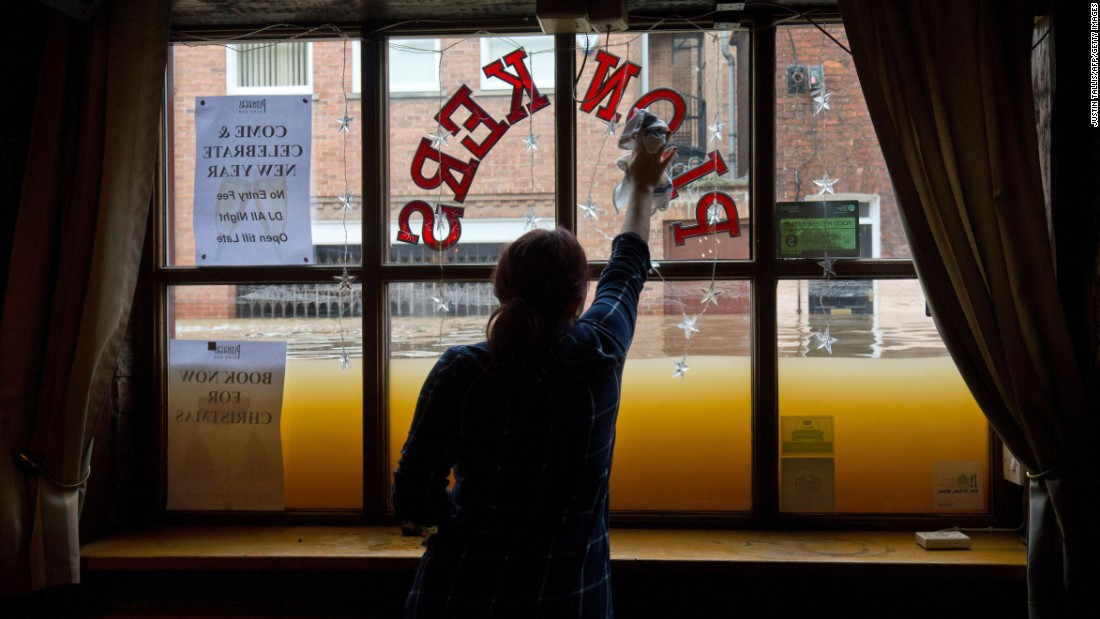 "A woman cleans the inside window of her wine bar as floodwaters rise in York, England, on Monday, December 28. Swaths of northern England have disappeared under <a href=""http://www.cnn.com/2015/12/27/europe/uk-flooding/"" target=""_blank"">mammoth flooding,</a> prompting evacuations and dozens of urgent warnings."