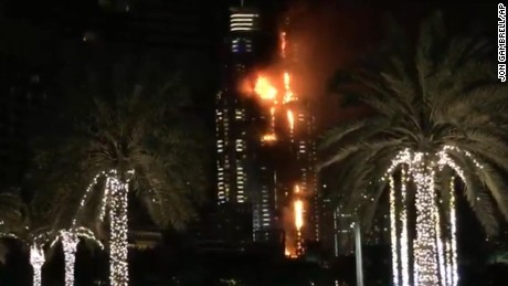 This image taken from AP video shows smoke and flames pouring from a residential building, which also contains the Address Downtown Hotel, in Dubai, United Arab Emirates, Thursday evening, Dec. 31, 2015. (AP Photo/Jon Gambrell)