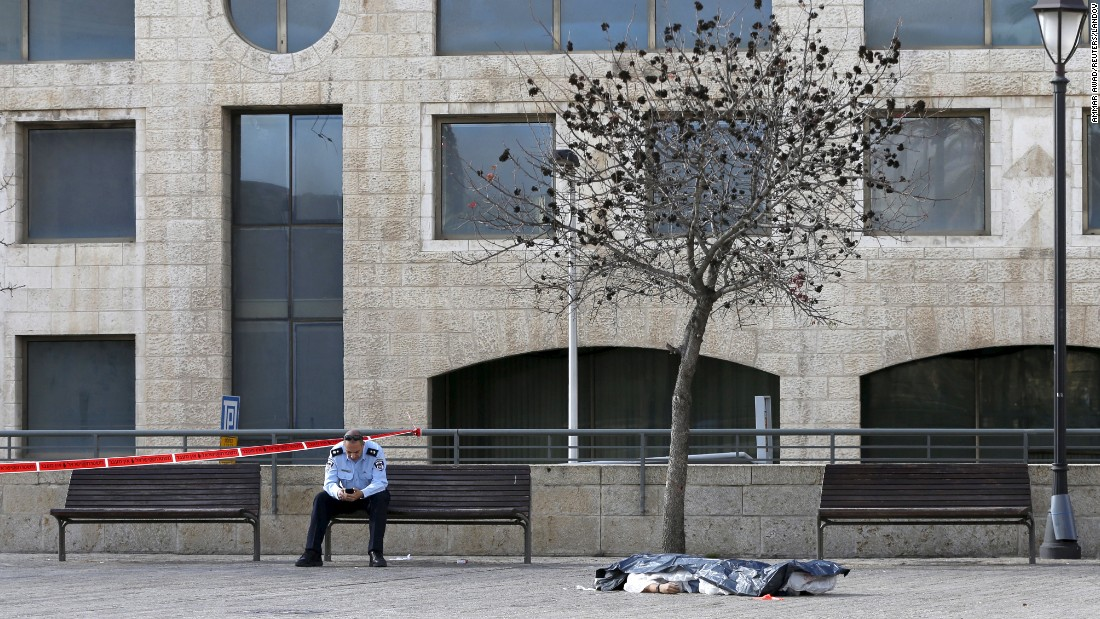An Israeli policeman sits next to the dead body of a Palestinian who, according to a police spokesperson, was fatally shot after he tried to stab an officer near Jerusalem's Old City on Saturday, December 26.