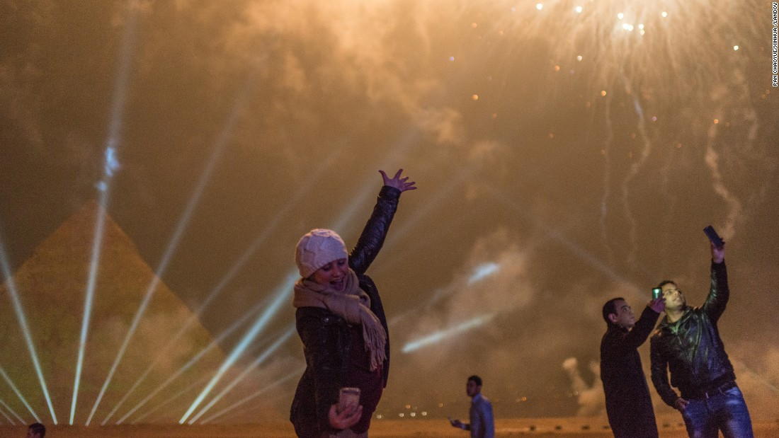 People take selfies during New Year celebrations at the pyramids in Giza, Egypt.