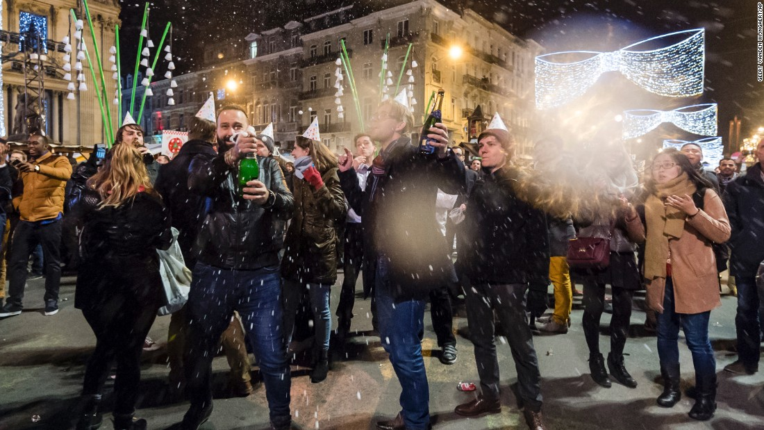 People pop bottles of champagne as they celebrate the new year in the historic center in Brussels.