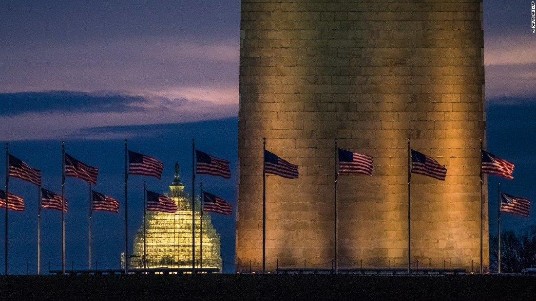 The U.S. Capitol is seen behind the Washington Monument as day breaks on Thursday, December 31.