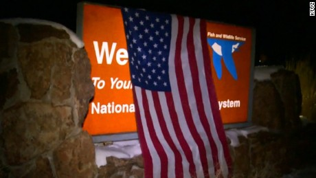 Protesters drape an American flag over the wildlife refuge's sign.