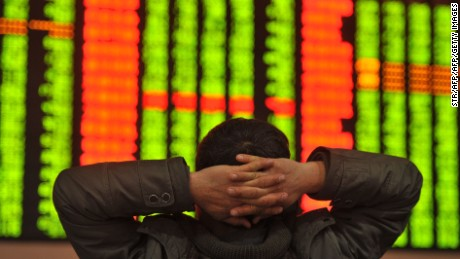 An investor sits in front of a screen showing stock market movements in a stock firm in Fuyang, east China's Anhui province.
