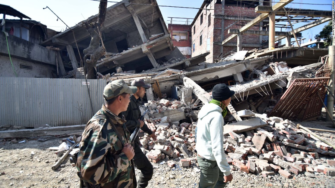 Security personnel walk past a collapsed building in Imphal, India, after a magnitude-6.7 earthquake on Monday, January 4.