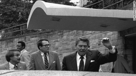 U.S. President Ronald Reagan winces and raises his left arm as he was shot by an assailant as he left a Washington hotel, Monday, March 30, 1981, after making a speech to a labor group. The President was shot in the upper left side.
