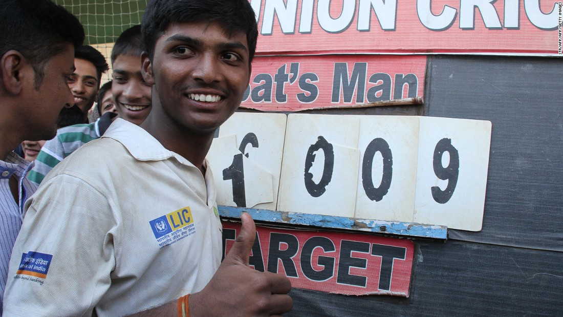 Pranav Dhanawade poses next to the scoreboard showing his historic innings of 1,009 not out.