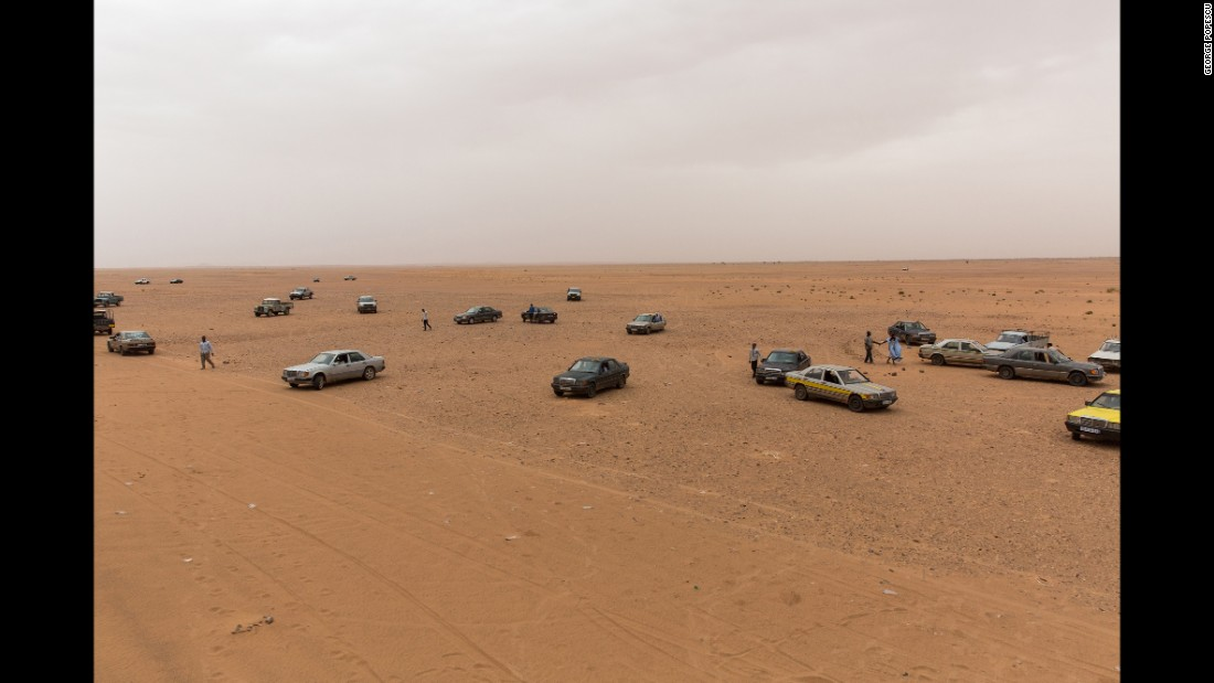 Cars wait on the outskirts of Zouérat to pick up passengers after the train ride.