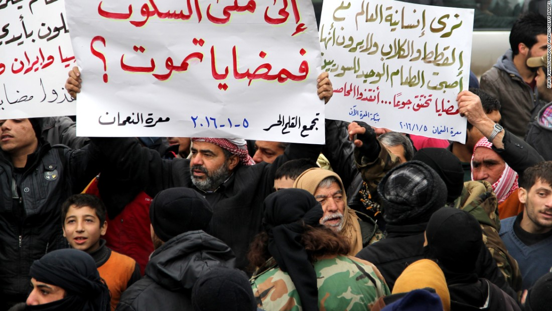 Demonstrators in Idlib, Syria, hold banners in a protest for civilians in besieged Madaya on Tuesday, January 5.