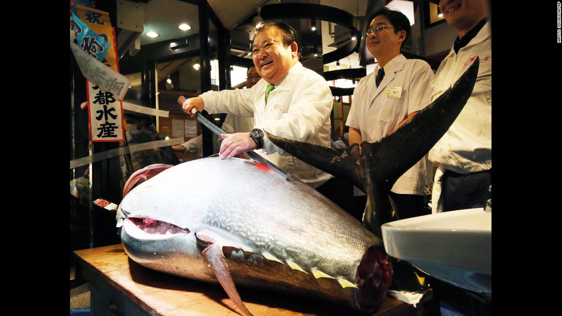 Kiyoshi Kimura, president of a company that runs a sushi restaurant chain, poses with a massive bluefin tuna at the Tsukiji Market in Tokyo on Tuesday, January 5. He bid the highest price -- 14 million yen, or nearly $120,000 -- for the tuna, which weighed nearly 200 kilograms (441 pounds).