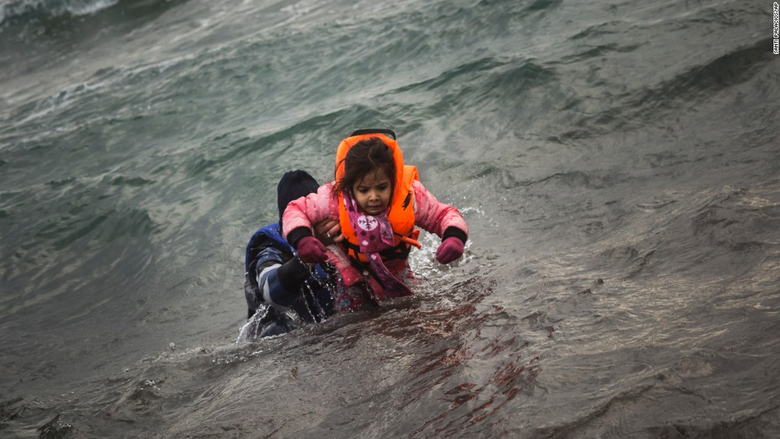 "A migrant carries a child to shore after their dinghy reached the Greek island of Lesbos on Sunday, January 3. <a href=""http://www.cnn.com/2015/10/25/world/cnnphotos-lesbos-migrants-items-left-behind/index.html"" target=""_blank"">The island has been overwhelmed</a> by refugees and migrants seeking a better life in Europe."