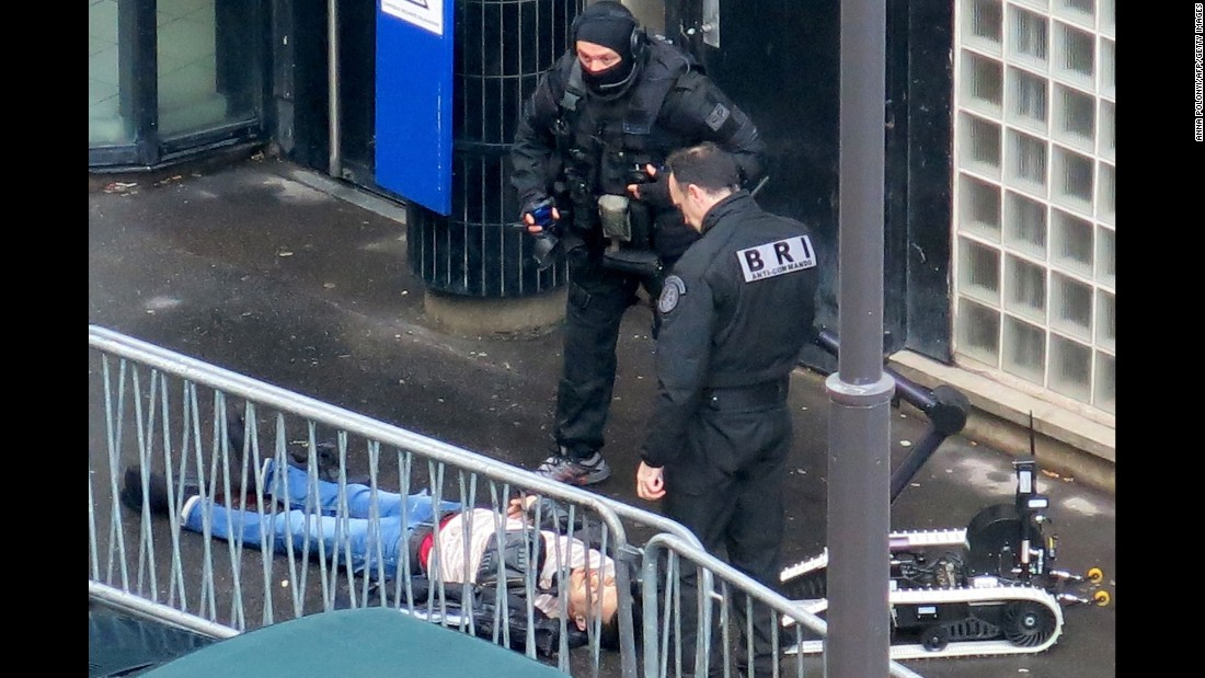 "Police officers stand over a knife-wielding man <a href=""http://www.cnn.com/2016/01/07/europe/paris-gunfire-charlie-hebdo-anniversary/"" target=""_blank"">who was shot as he attempted to enter a police station</a> in the northern Paris neighborhood of Barbes on Thursday, January 7. He was carrying a fake explosive device, and an image of the ISIS flag was found on his body, said a statement from the Paris prosecutor's office."