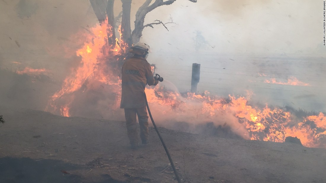 Firefighters from the Bunbury Volunteer Bushfire Brigade fight the flames.