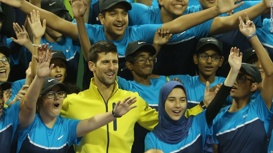 Novak Djokovic poses for a picture with the tournament's ballboys and girls after thrashing Rafael Nadal of Spain in the final Qatar Open in Doha.