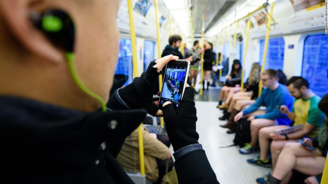 A commuter takes a photo of participants traveling on a London underground train.