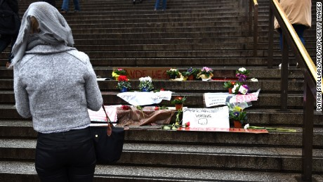 A woman looks at flowers and messages laid on steps in front of Cologne's main train station.