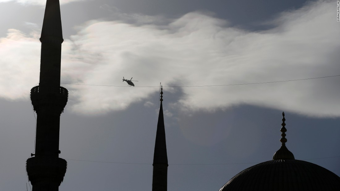 A police helicopter patrols over the historic Sultanahmet district.