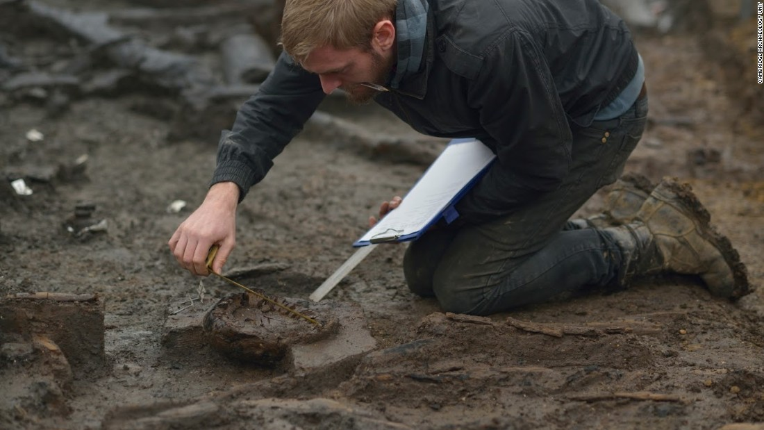 Wood specialist Mike Bamforth examines the base of a Bronze Age wooden bucket.