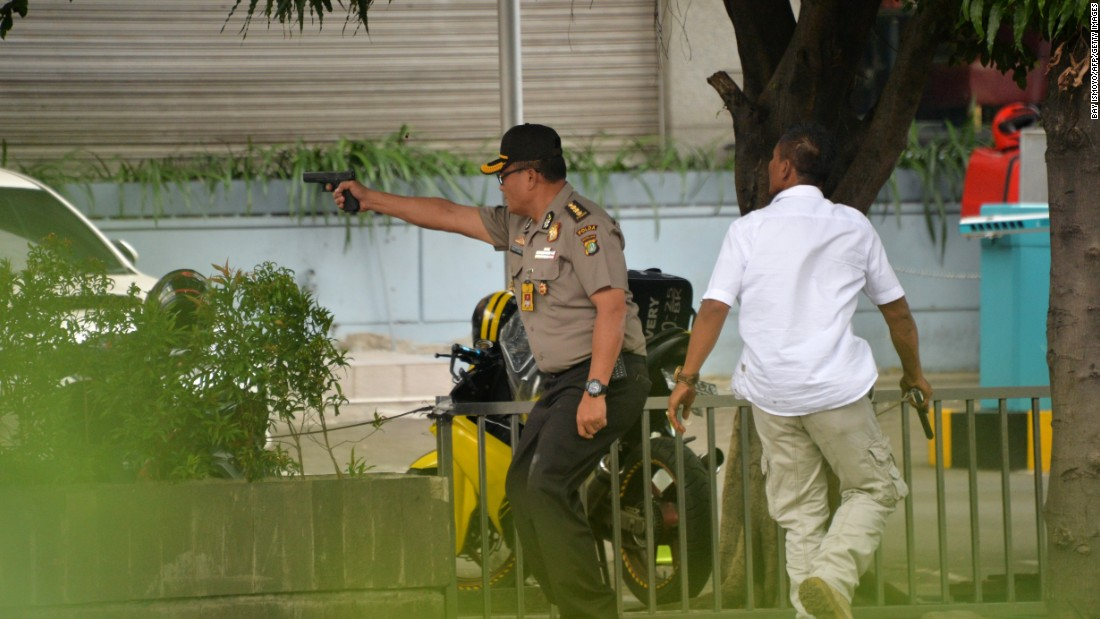 A policeman fires his handgun towards suspects outside a cafe on January 14.