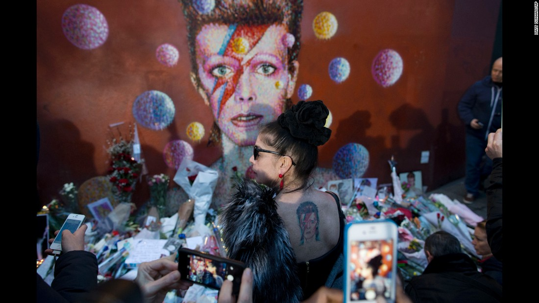"A woman with a David Bowie tattoo poses in front of a Bowie mural in London on Monday, January 11. The rock legend <a href=""http://www.cnn.com/2016/01/11/entertainment/david-bowie-death/"" target=""_blank"">died a day earlier</a> after an 18-month battle with cancer. He was 69."