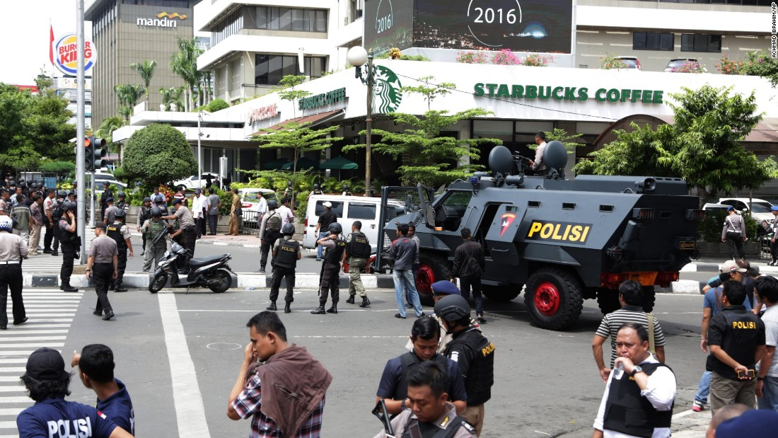 Police officers stand guard outside a Starbucks cafe in Jakarta's bustling shopping area, near the site of an explosion, on January 14.