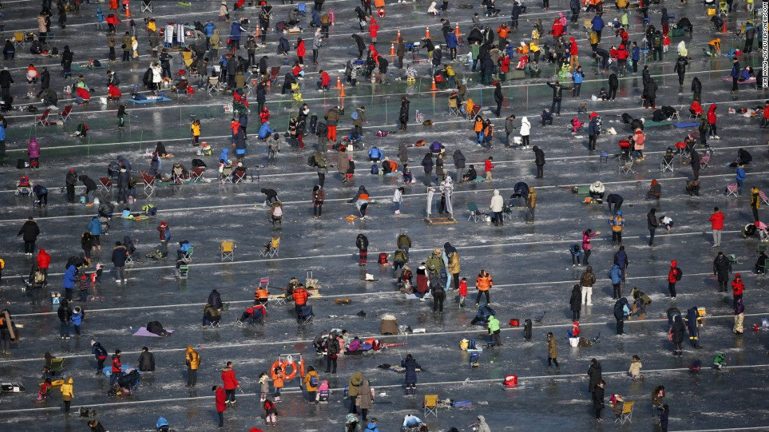 People fish for trout at a frozen river in Hwacheon, South Korea, on Saturday, January 9.