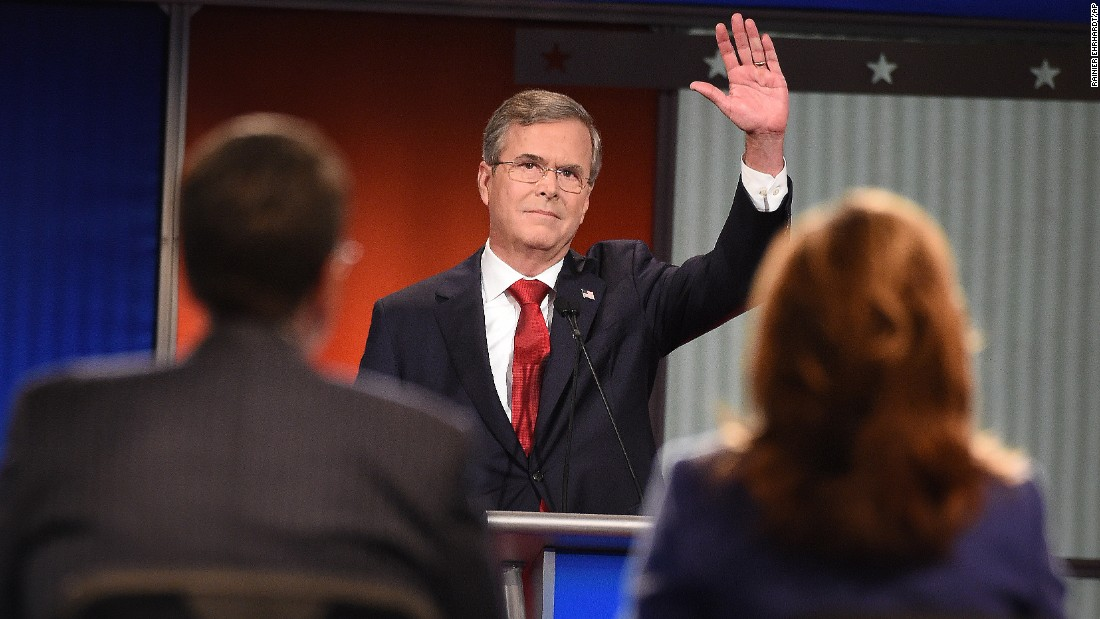 "Bush waves to the audience. The former Florida governor has been trying to build momentum that he had in the early stages of his candidacy, and he went after Democratic candidate Hillary Clinton early in the debate. ""She's under investigation with the FBI right now,"" he said. ""If she gets elected, her first 100 days, instead of setting an agenda, she might be going back and forth between the White House and the courthouse. We need to stop that."""