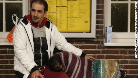 A Syrian hoping for Danish asylum lets his daughter rest in a German train station near Denmark.
