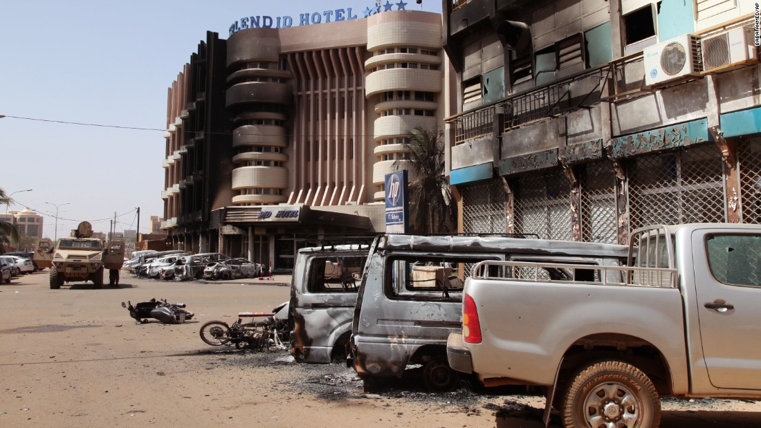 Burnt-out cars sit in front of the Splendid Hotel after an overnight attack in Ouagadougou, Burkina Faso, on Saturday, January 16. Attackers raided the luxury hotel late Friday, opening fire and seizing hostages in a siege that lasted several hours and ended with at least 23 people dead.